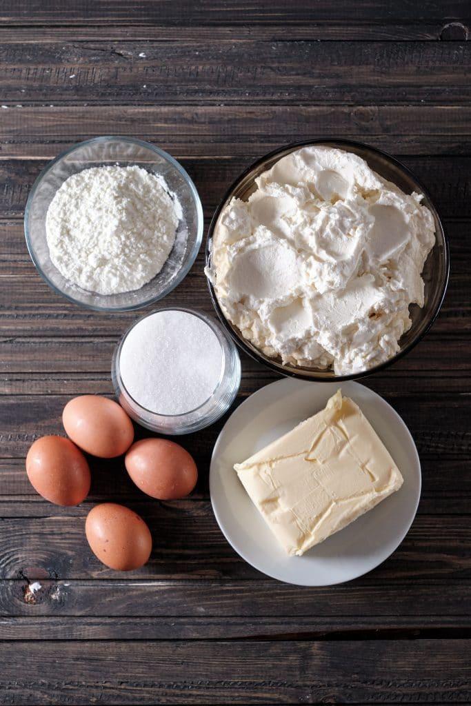 Składniki na dietetyczny sernik bez cukru - twaróg, budyń, jajka, masło i opcjonalny cukier (lub inny słodzik - stewia, ksylitol).