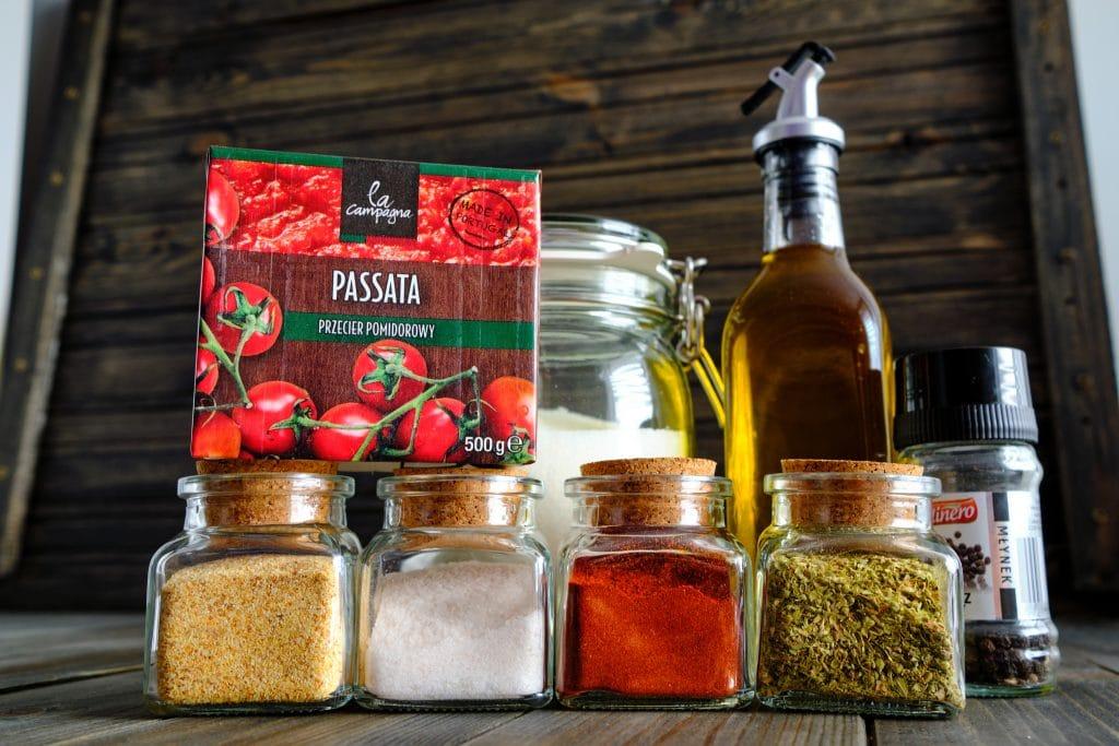 Składniki na sos pomidorowy do pizzy - pomidory, sól, pieprz, cukier, oliwa, czosnek, papryka i oregano.